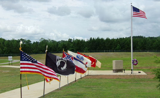 The Ripley Memorial Day Program 2017 Flag display with the site of the future Tippah County Veterans Memorial Park in the background